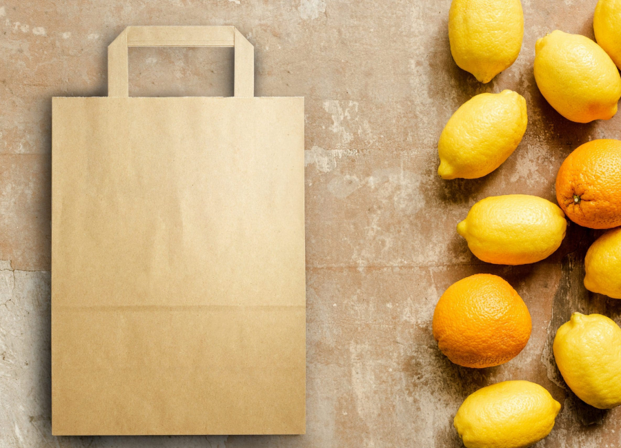 Top View of Lemons And Oranges Near Paper Bag on Weathered Surface